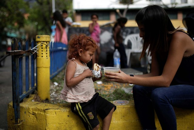 A volunteer of Make The Difference (Haz La Diferencia) charity initiative gives a cup of soup and an arepa to a homeless child  in a street of Caracas, Venezuela March 5, 2017. Picture taken March 5, 2017. REUTERS/Marco Bello