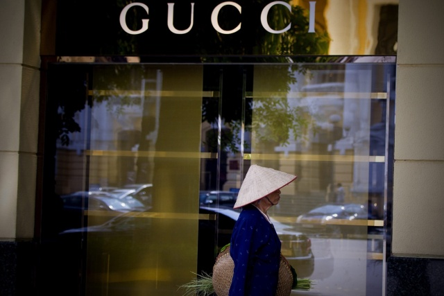LIN02 HANOI (VIETNAM) 18/09/2013.- Una mujer camina junto a una tienda de Gucci en Hanoi (Vietnam) hoy, miércoles 18 de septiembre de 2013. Los millonarios en Vietnam han aumentado en un 14,7 por ciento en 2013. Un total de 195 personas tienen un patrimonio por encima de los 30 millones de dólares. EFE/Luong Thai Linh