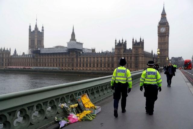 En la imagen, agentes de policía pasan por delante de ofrendas florales situadas en la escena del ataque en Westminster Bridge, en Londres, 24 de marzo de 2017. La policía británica dijo que realizó dos nuevos arrestos de carácter significativo en la investigación del ataque en el Parlamento de Londres y reveló el nombre de nacimiento del presunto autor, que se llamaría Adrian Russell Ajao. REUTERS/Darren Staples
