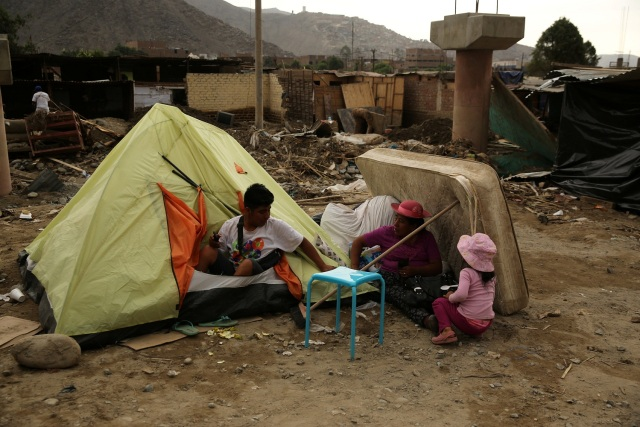 Family stands outside a tent after rivers breached their banks due to torrential rains, causing flooding and widespread destruction in Huachipa, Lima, Peru, March 24, 2017. REUTERS/Mariana Bazo