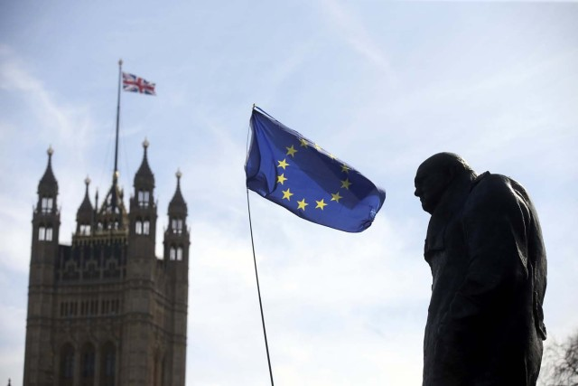 An EU flag flies between the statue of Winston Churchill and a Union Flag flying from the Big Ben clock tower, during a Unite for Europe rally in Parliament Square, in central London, Britain March 25, 2017. REUTERS/Paul Hackett
