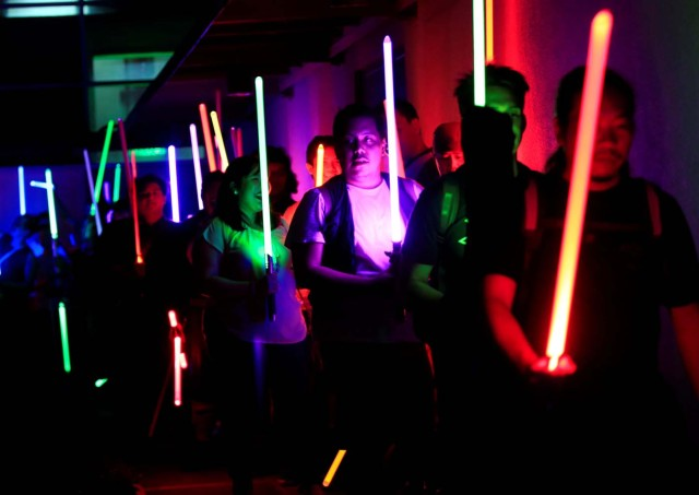 Star Wars enthusiasts raise their lightsabers as they participate in the annual Earth Hour, an hour of lights out to raise awareness on climate change, in Taguig city, metro Manila, Philippines March 25, 2017. REUTERS/Romeo Ranoco