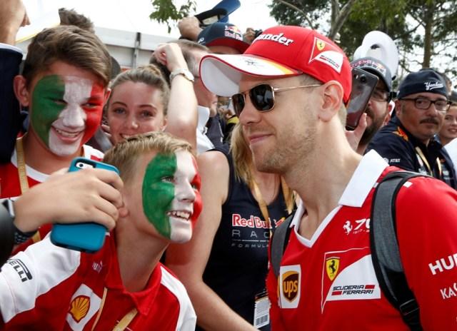 Formula One - F1 - Australian Grand Prix - Melbourne, Australia - 26/03/2017 Ferrari driver Sebastian Vettel of Germany poses with a fan as he arrives at the track. REUTERS/Brandon Malone