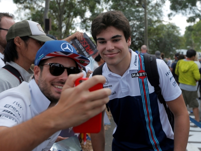 Formula One - F1 - Australian Grand Prix - Melbourne, Australia - 26/03/2017 Williams driver Lance Stroll (R) poses for a selfie with a fan as he arrives at the track. REUTERS/Jason Reed