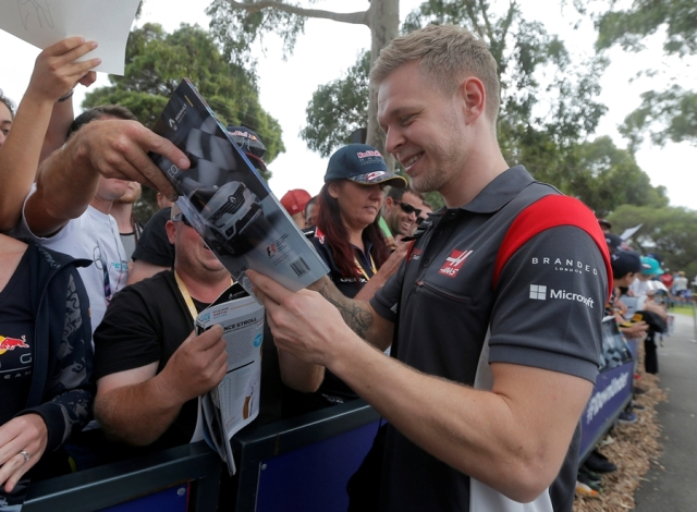 Formula One - F1 - Australian Grand Prix - Melbourne, Australia - 26/03/2017 Haas driver Kevin Magnussen of Denmark signs an autograph as he arrives at the track. REUTERS/Jason Reed