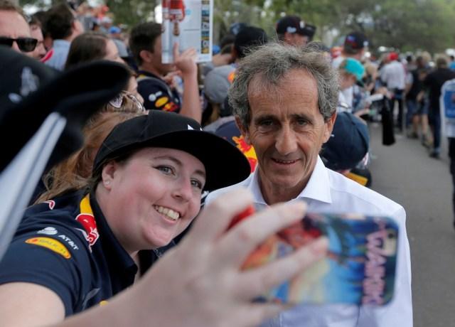 Formula One - F1 - Australian Grand Prix - Melbourne, Australia - 26/03/2017 Former Formula One world champion Alain Prost of France takes a selfie as he arrives at the track. REUTERS/Jason Reed