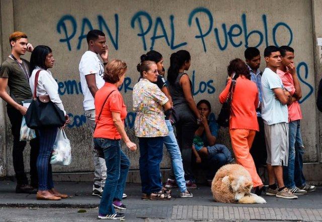 Gente haciendo cola para comprar pan fuera de una panadería en Caracas el 17 de marzo de 2017. Credit Juan Barreto/Agence France-Presse