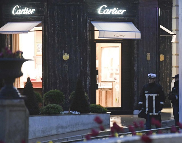 Monaco's police officers stand guard in front of the Cartier jewellery boutique after it was robbed in downtown Monaco on March 25, 2017. Monaco police were hunting for two suspects on March 25 after a daring afternoon robbery at the famous French jeweller Cartier, prompting a brief lockdown of the tiny principality and jet set haven. / AFP PHOTO / Yann COATSALIOU