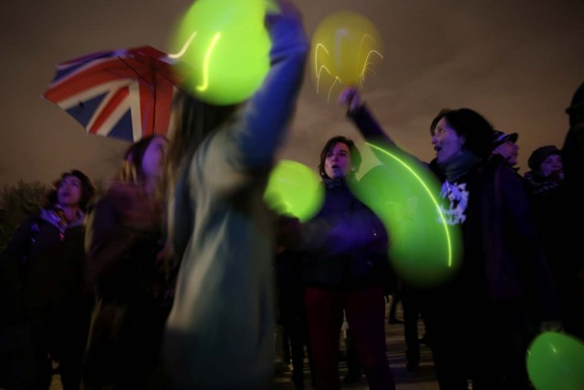 People play with lit balloons after the lights were switched off for Earth Hour at the Royal Palace in Madrid, Spain, March 25, 2017. REUTERS/Susana Vera