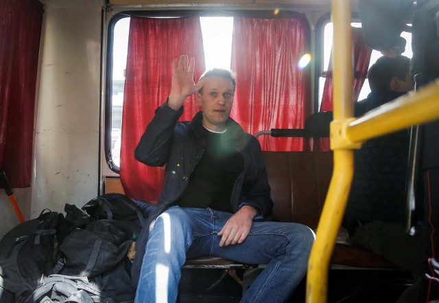 Anti-corruption campaigner and opposition figure Alexei Navalny waves as he sits inside a police van after after being detained during a rally in Moscow, Russia, March 26, 2017. REUTERS/Maxim Shemetov