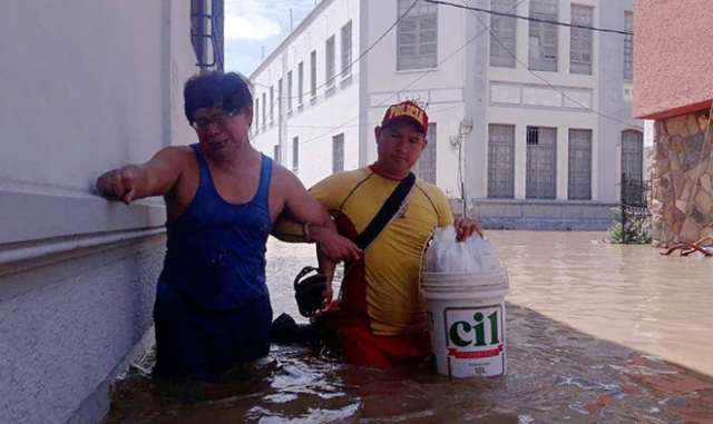 Residents in the city of Piura, 1,000 kilometres north of Lima, wade through water on the streets on March 27, 2017, after nearly 15 hours of rain caused the Piura River to overflow, flooding neighbourhoods in most of the city.  The El Nino climate phenomenon is causing muddy flash floods and rivers to overflow along the entire Peruvian coast, isolating communities and neighborhoods. Most cities face water shortages as water lines have been compromised by mud and debris. / AFP PHOTO / PATRICIA LACHIRA / BEST QUALITY AVAILABLE