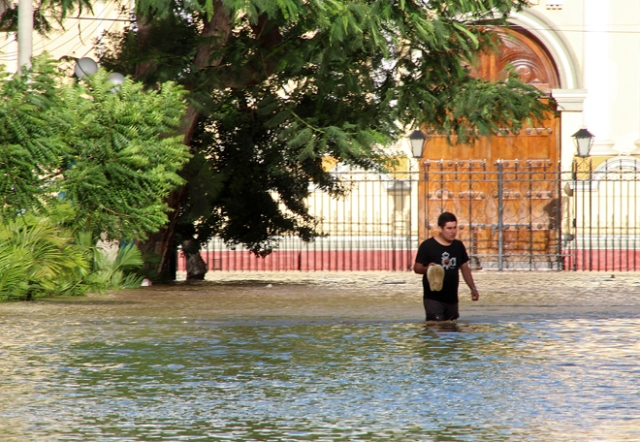 Residents in the city of Piura, 1,000 kilometres north of Lima, wade through water on the streets on March 27, 2017, after nearly 15 hours of rain caused the Piura River to overflow, flooding neighbourhoods in most of the city.  The El Nino climate phenomenon is causing muddy flash floods and rivers to overflow along the entire Peruvian coast, isolating communities and neighborhoods. Most cities face water shortages as water lines have been compromised by mud and debris. / AFP PHOTO / PATRICIA LACHIRA