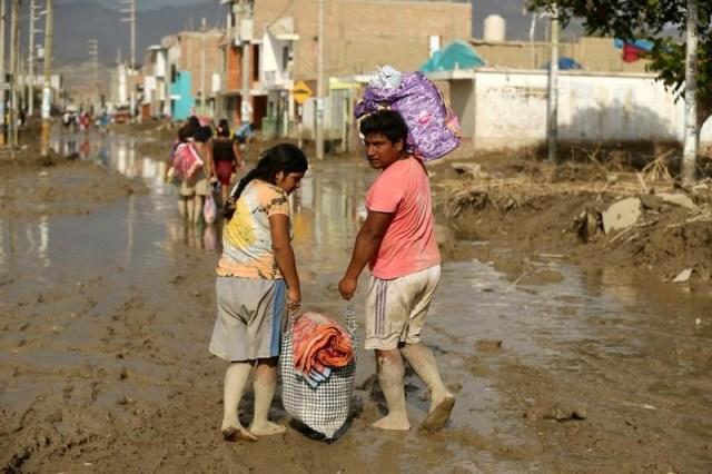 Personas cruzan una calle inundada tras el desborde de ríos por las lluvias torrenciales en Huarmey, Perú. 22 de marzo 2017. El Banco Central de Perú recortó el viernes su proyección de crecimiento económico y no descarta bajar la tasa de interés para ayudar a impulsar la demanda interna, en momentos en que el país sufre sus peores inundaciones en dos décadas. REUTERS/Mariana Bazo