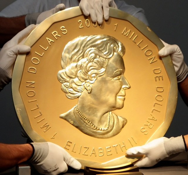 "FILE PHOTO - Picture taken in Vienna, Austria on June 25, 2010 shows experts of an Austrian art forwarding company holding one of the world's largest gold coins, a 2007 Canadian $ 1,000,000 ""Big Maple Leaf"". An identical coin was stolen from Berlin's Bode Museum on March 27, 2017. REUTERS/Heinz-Peter Bader/File Photo"