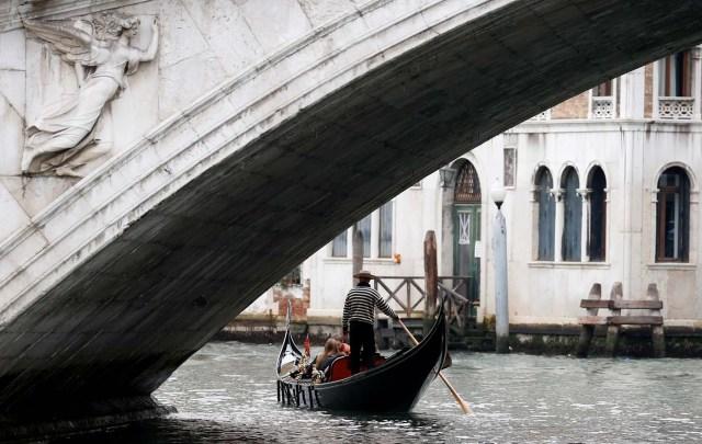 FILE PHOTO: A gondolier rows past the Rialto bridge in Venice, Italy October 13, 2013. REUTERS/Stefano Rellandini/File Photo