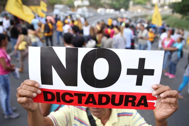 "Opposition supporters holding a placard that reads, ""No more dictatorship"" shout slogans as they block a highway during a protest against Venezuelan President Nicolas Maduro's government in Caracas, Venezuela March 31, 2017. REUTERS/Carlos Garcia Rawlins"