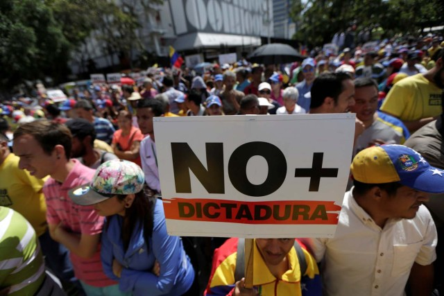 "An opposition supporter holds a placard that reads ""No more dictatorship"" as he takes part in a rally against Venezuela's President Nicolas Maduro's government in Caracas, Venezuela April 1, 2017. REUTERS/Marco Bello"
