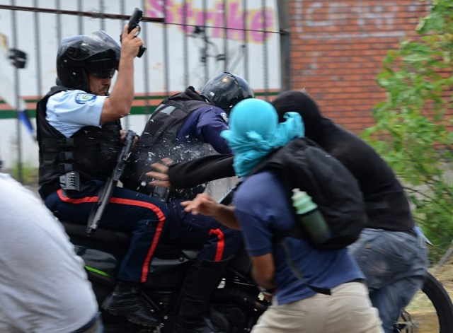 Students opposing Venezuelan President Nicolas Maduro scuffle with policemen on a motorcycle during a demonstration in San Cristobal, Venezuela on April 5, 2017. University students and police clashed Wednesday during a protest in the Venezuelan city of San Cristobal (western border with Colombia), with a balance of at least a dozen injured. / AFP PHOTO / George Castellanos