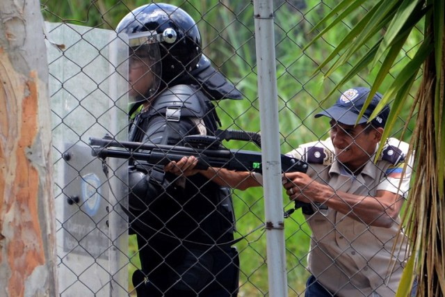 A policeman aims a shotgun at students opposing Venezuelan President Nicolas Maduro demonstrating in San Cristobal, Venezuela on April 5, 2017. University students and police clashed Wednesday during a protest in the Venezuelan city of San Cristobal (western border with Colombia), with a balance of at least a dozen injured. / AFP PHOTO / George Castellanos