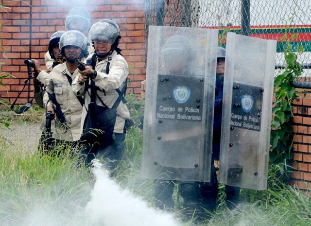 Riot police fire tear gas and rubber bullets at students opposing Venezuelan President Nicolas Maduro marching to protest in San Cristobal, Venezuela on April 5, 2017. University students and police clashed Wednesday during a protest in the Venezuelan city of San Cristobal (western border with Colombia), with a balance of at least a dozen injured. / AFP PHOTO / George Castellanos