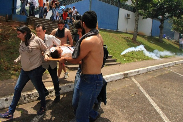 A demonstrator injured after riot police fired tear gas and rubber bullets at students opposing Venezuelan President Nicolas Maduro who were marching to protest in San Cristobal is carried away by other protesters, in San Ceistobal, Venezuela on April 5, 2017. University students and police clashed Wednesday during a protest in the Venezuelan city of San Cristobal (western border with Colombia), with a balance of at least a dozen injured. / AFP PHOTO / George Castellanos