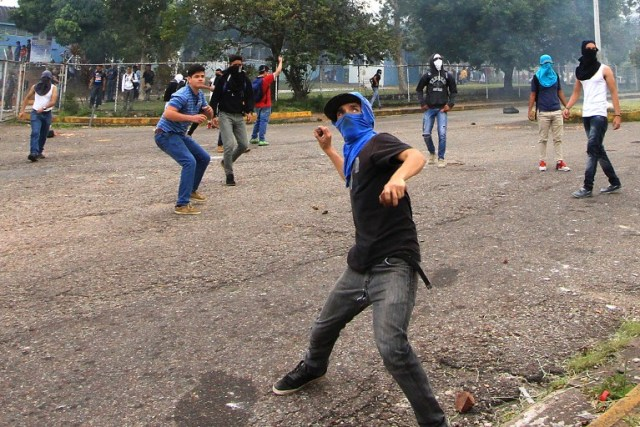 Students opposing Venezuelan President Nicolas Maduro throw stones at riot police during a protest in San Cristobal, Venezuela on April 5, 2017. University students and police clashed Wednesday during a protest in the Venezuelan city of San Cristobal (western border with Colombia), with a balance of at least a dozen injured. / AFP PHOTO / George Castellanos