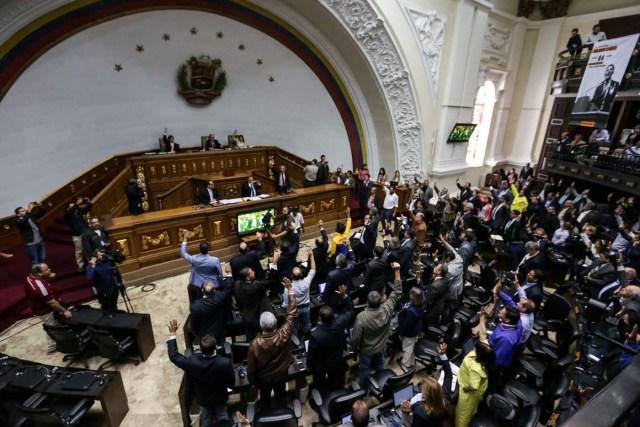 """CAR03. CARACAS (VENEZUELA), 05/04/2017.- Diputados de la Asamblea Nacional votan hoy, miércoles 5 de abril de 2017, durante un sesión del Parlamento en Caracas (Venezuela). El Parlamento venezolano, controlado por la oposición, acordó hoy responsabilizar al presidente del país, el chavista Nicolás Maduro, del supuesto """"golpe de estado"""" perpetrado por el desconocimiento del Poder Legislativo a través de las sentencias del Tribunal Supremo, que le mantiene en """"desacato"""". EFE/CRISTIAN HERNANDEZ"""