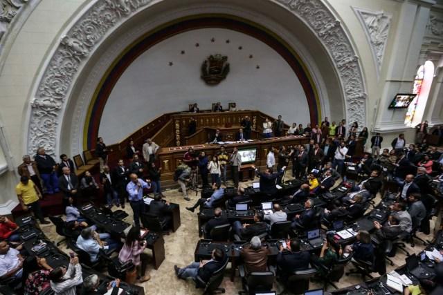 """CAR11. CARACAS (VENEZUELA), 05/04/2017.- Diputados de la Asamblea Nacional votan hoy, miércoles 5 de abril de 2017, durante un sesión del Parlamento en Caracas (Venezuela). El Parlamento venezolano, controlado por la oposición, acordó hoy responsabilizar al presidente del país, el chavista Nicolás Maduro, del supuesto """"golpe de estado"""" perpetrado por el desconocimiento del Poder Legislativo a través de las sentencias del Tribunal Supremo, que le mantiene en """"desacato"""". EFE/CRISTIAN HERNANDEZ"""