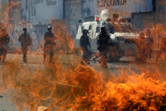 Venezuelan national guards walk behind a burning blockade during clashes with demonstrators during an opposition rally in Caracas, Venezuela, April 6, 2017. REUTERS/Marcos Bello