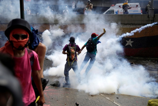 Demonstrators are seen amidst tear gas fired by police during an opposition rally in Caracas, Venezuela, April 6, 2017. REUTERS/Marco Bello