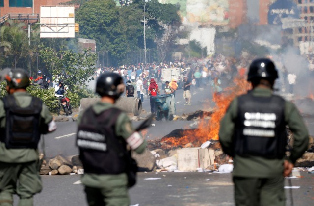 Venezuelan national guards stand behind a burning blockade during clashes with demonstrators during an opposition rally in Caracas, Venezuela, April 6, 2017. REUTERS/Carlos Garcia Rawlins