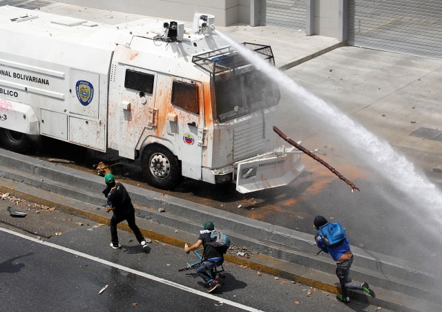 A police water cannon disperses demonstrators during an opposition rally in Caracas, Venezuela April 6, 2017. REUTERS/Christian Veron