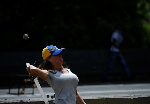 A demonstrator throws an object toward policemen during an opposition rally in Caracas, Venezuela April 6, 2017. REUTERS/Carlos Garcia Rawlins