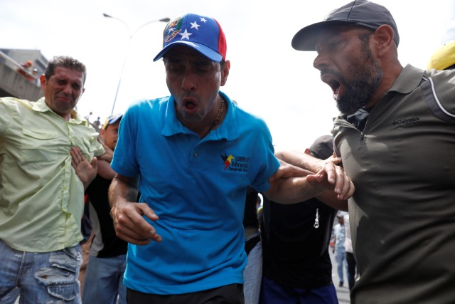 Opposition leader Henrique Capriles reacts after being exposed to tear gas during an opposition rally in Caracas, Venezuela April 6, 2017. REUTERS/Carlos Garcia Rawlins
