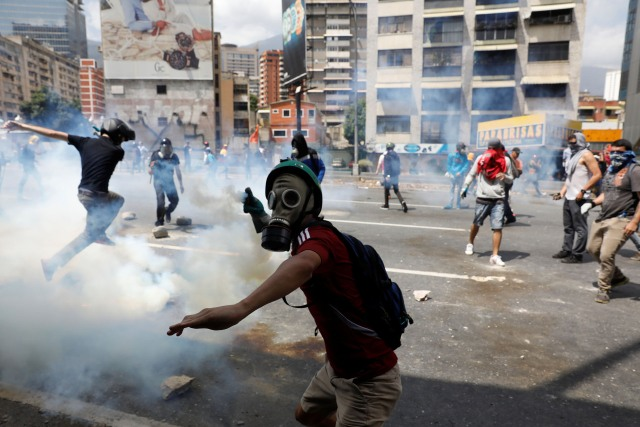 A demonstrator throws a tear gas canister back to policemen during an opposition rally in Caracas, Venezuela April 6, 2017. REUTERS/Carlos Garcia Rawlins