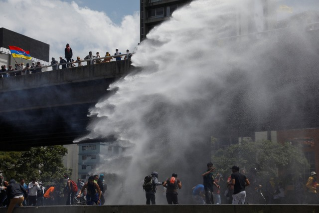 Police use a water cannon to disperse demonstrators during an opposition rally in Caracas, Venezuela April 6, 2017. REUTERS/Carlos Garcia Rawlins