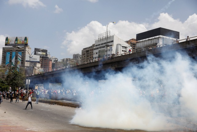 Demonstrators stay away from tear gas fired by security forces during an opposition rally in Caracas, Venezuela April 6, 2017. REUTERS/Carlos Garcia Rawlins