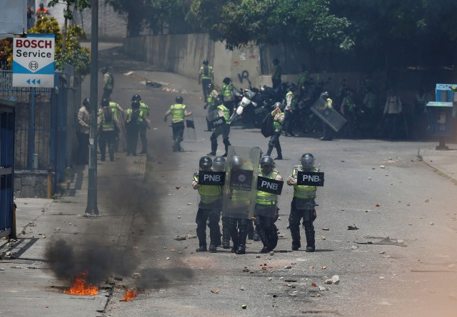 Policemen cover themselves from objects thrown by demonstrators during an opposition rally in Caracas, Venezuela April 6, 2017. REUTERS/Carlos Garcia Rawlins