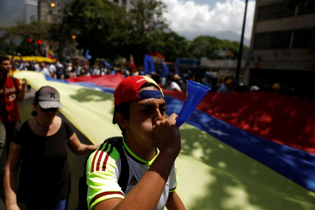 Demonstrators march holding a giant national flag during an opposition rally in Caracas, Venezuela April 6, 2017. REUTERS/Carlos Garcia Rawlins