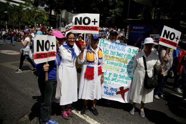 """Catholic nuns hold placards reading """"No more Dictatorship"""" during an opposition rally in Caracas, Venezuela April 6, 2017. REUTERS/Marco Bello"""