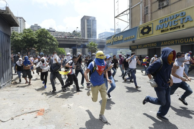 Venezuelan opposition activists run during protests against the government of President Nicolas Maduro on April 6, 2017 in Caracas. The center-right opposition vowed fresh street protests -after earlier unrest left dozens of people injured - to increase pressure on Maduro, whom they blame for the country's economic crisis. / AFP PHOTO / FEDERICO PARRA