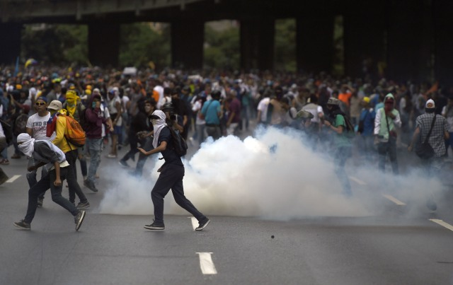 Venezuelan opposition activists hold a protest against the government of President Nicolas Maduro on April 6, 2017 in Caracas. The center-right opposition vowed fresh street protests -after earlier unrest left dozens of people injured - to increase pressure on Maduro, whom they blame for the country's economic crisis. / AFP PHOTO / JUAN BARRETO