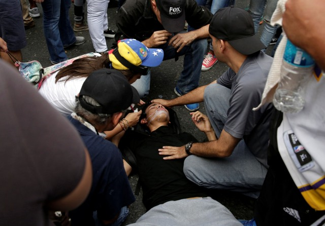 Demonstrators attend to a fellow protester during an opposition rally in Caracas, Venezuela, April 6, 2017. REUTERS/Carlos Garcia Rawlins