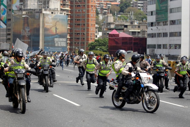 Police withdraw as demonstrators run toward them during an opposition rally in Caracas, Venezuela, April 6, 2017. REUTERS/Christian Veron