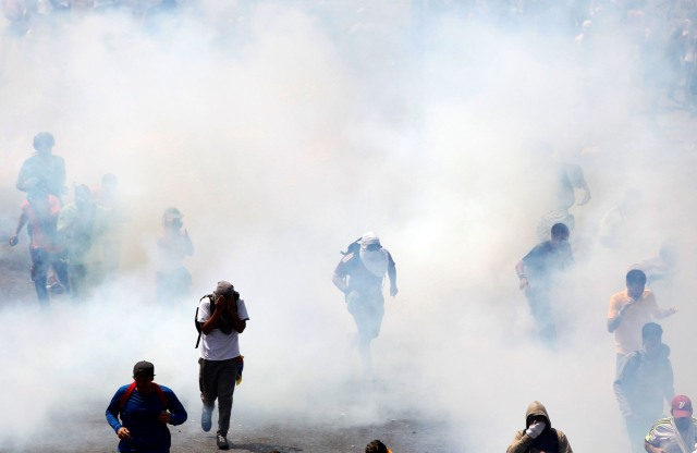 Demonstrators run from tear gas during clashes with security forces at an opposition rally in Caracas, Venezuela, April 6, 2017. REUTERS/Christian Veron