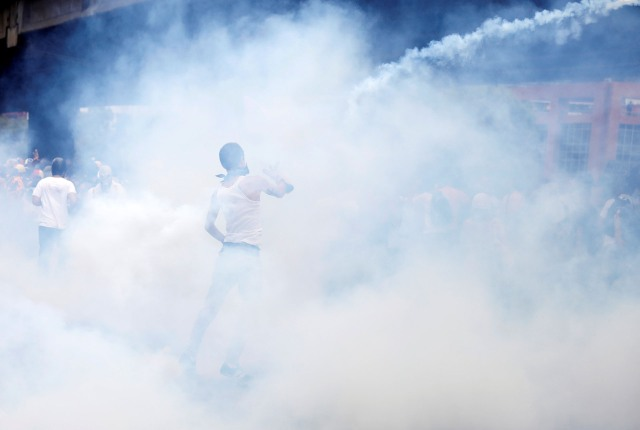 A demonstrator throws back a tear gas canister during clashes with security forces at an opposition rally in Caracas, Venezuela, April 6, 2017. REUTERS/Carlos Garcia Rawlins