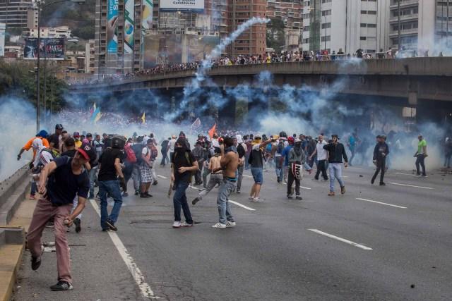 CAR01. CARACAS (VENEZUELA), 06/04/2017 - Un grupo de personas participa en una manifestación de opositores al gobierno de Nicolás Maduro hoy, jueves 6 de abril de 2017, en Caracas (Venezuela). La Policía Nacional Bolivariana (PNB) dispersó hoy con gases lacrimógenos y agua una marcha opositora en Caracas que pretendía llegar hasta la Defensoría del Pueblo para pedir su respaldo al proceso iniciado por el Parlamento contra siete magistrados del Tribunal Supremo de Justicia (TSJ). EFE/MIGUEL GUTIERREZ