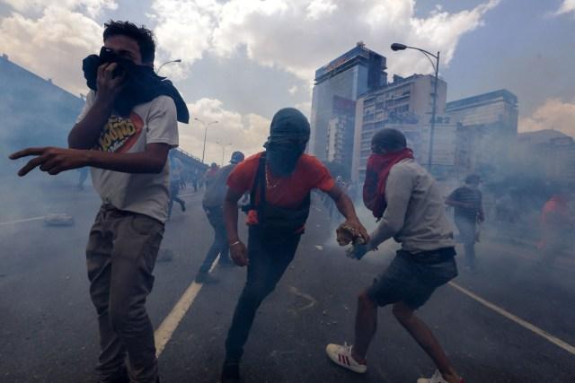 CAR01. CARACAS (VENEZUELA), 06/04/2017 - Un grupo de personas participa en una manifestación de opositores al gobierno de Nicolás Maduro hoy, jueves 6 de abril de 2017, en Caracas (Venezuela). La Policía Nacional Bolivariana (PNB) dispersó hoy con gases lacrimógenos y agua una marcha opositora en Caracas que pretendía llegar hasta la Defensoría del Pueblo para pedir su respaldo al proceso iniciado por el Parlamento contra siete magistrados del Tribunal Supremo de Justicia (TSJ). EFE/CRISTIAN HERNÁNDEZ
