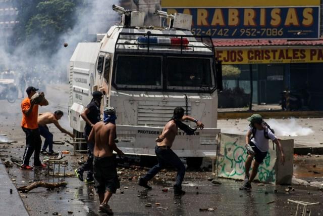 CAR01. CARACAS (VENEZUELA), 06/04/2017 - Efectivos de la Policía Nacional Bolivariana (PNB) dispersan una manifestación de opositores al gobierno de Nicolás Maduro hoy, jueves 6 de abril de 2017, en Caracas (Venezuela). La Policía Nacional Bolivariana (PNB) dispersó hoy con gases lacrimógenos y agua una marcha opositora en Caracas que pretendía llegar hasta la Defensoría del Pueblo para pedir su respaldo al proceso iniciado por el Parlamento contra siete magistrados del Tribunal Supremo de Justicia (TSJ). EFE/CRISTIAN HERNÁNDEZ