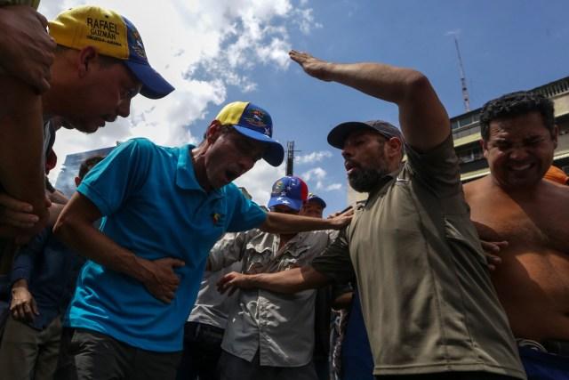 """CAR01. CARACAS (VENEZUELA), 06/04/2017 - El líber opositor venezolano Henrique Capriles (c) es afectado por gases lacrimógenos durante una manifestación contra el gobierno venezolano hoy, jueves 6 de abril de 2017, en Caracas (Venezuela). La alianza de partidos Mesa de la Unidad Democrática (MUD), contraria al Gobierno de Nicolás Maduro, aseguró hoy que los venezolanos se manifestaron este jueves en ocho ciudades de Venezuela en contra de los magistrados del Tribunal Supremo de Justicia (TSJ) a quienes acusan de haber dado un """"golpe de Estado"""". EFE/CRISTIAN HERNÁNDEZ"""